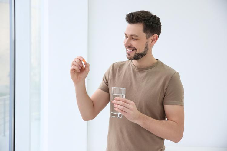 Young man taking vitamin indoors.
