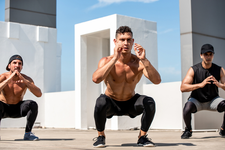 Group of fit sports men doing squat bodyweight workout training outdoors on building rooftop in sunlight.