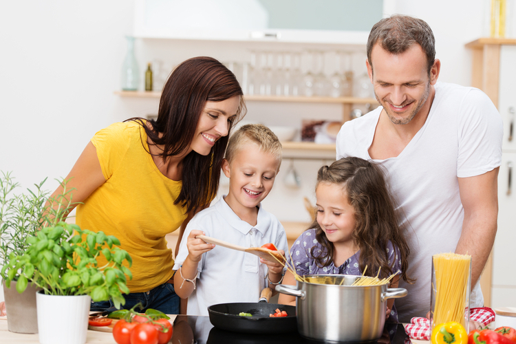 Happy young family with Mom and Dad and two young children cooking in the kitchen.