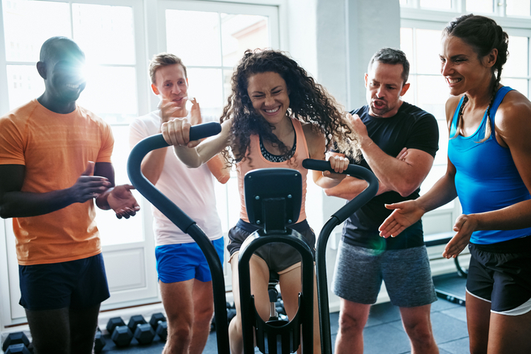 Group of people cheering on their female friend riding a stationary bike while working out together in a gym.