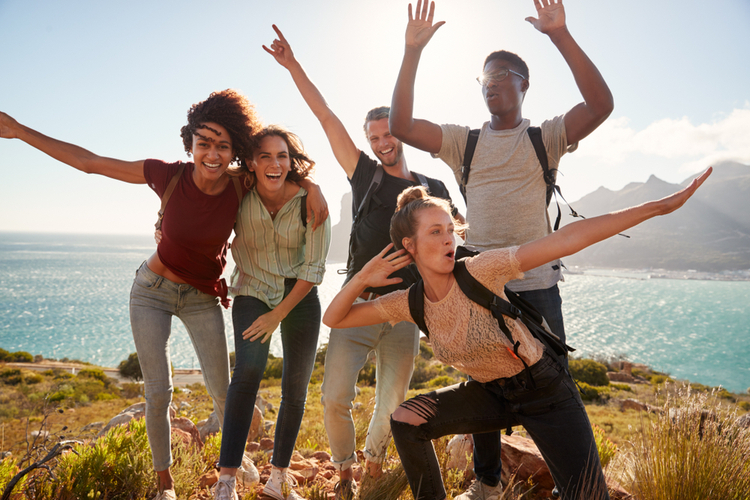 Friends on a hiking trip celebrate reaching the summit and have fun posing for photos.