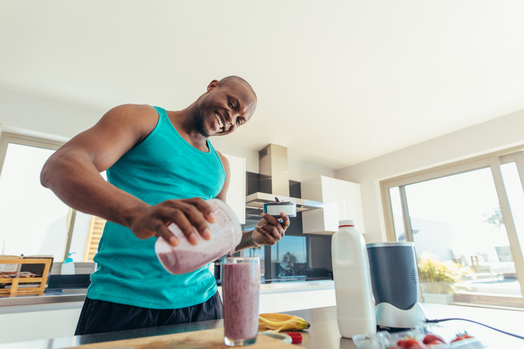 Smiling man pouring milkshake in a glass for drinking.