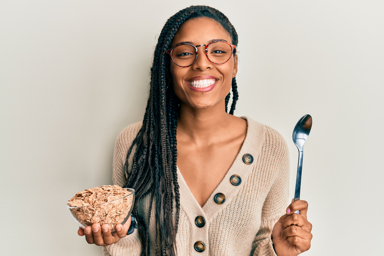 Woman eating healthy whole grain cereals smiling.