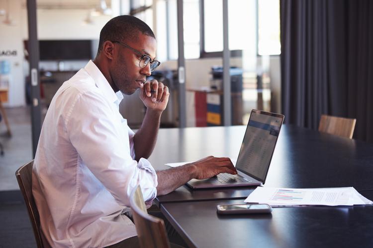 Man wearing glasses using laptop in office.
