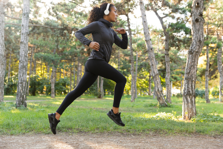 Image of feminine woman adidas ultimafusion and headphones working out while running through green park.