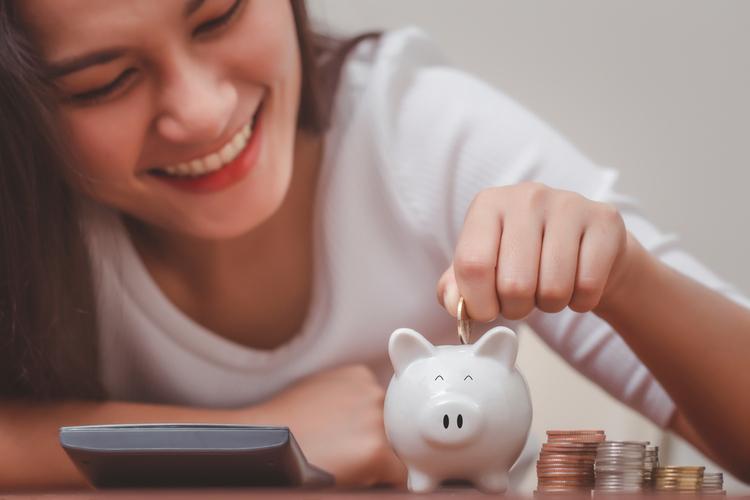 Woman hand putting money into piggy bank for saving money.