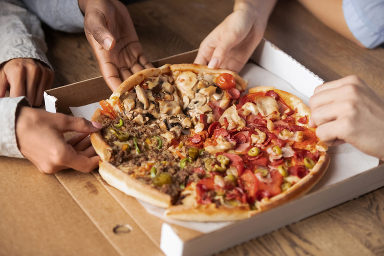 Close up hands of multi-ethnic people sharing a box of pizza.