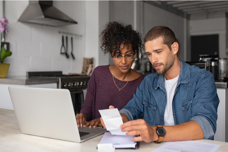Couple sitting in front a computer while doing their budget and thinking of ideas to make money.