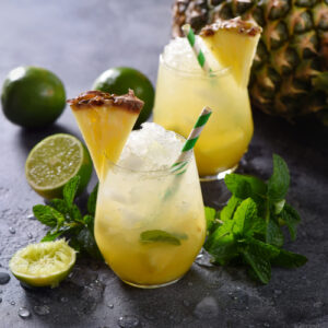 Cold pineapple cocktail with crushed ice, lime and mint, refreshing lemonade drink.