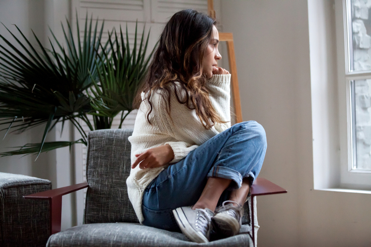 Woman sits on chair feels depressed.