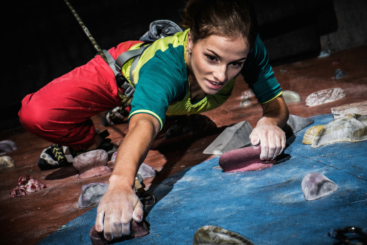 Young woman practicing rock-climbing on a rock wall indoors.