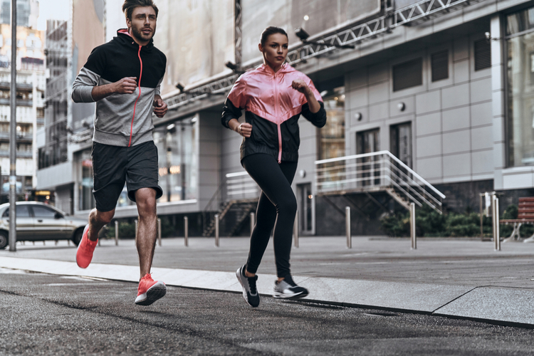 Full length of young couple in sport clothing running with runner's durable manual in mind.