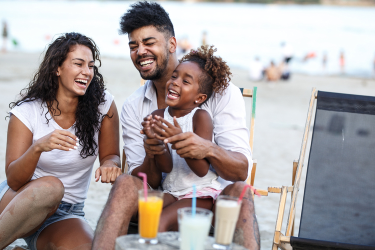Young mixed race family sitting and relaxing at the beach with summer drinks on beautiful summer day.