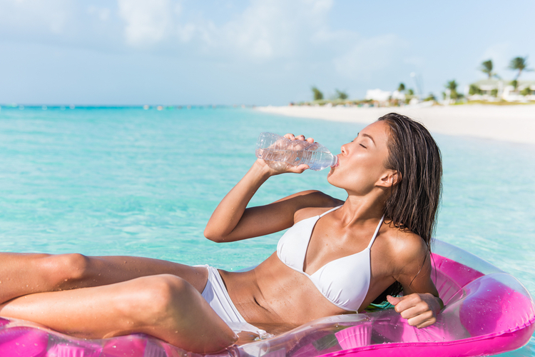 Beach vacation woman on summer holiday drinking fresh and clean water.