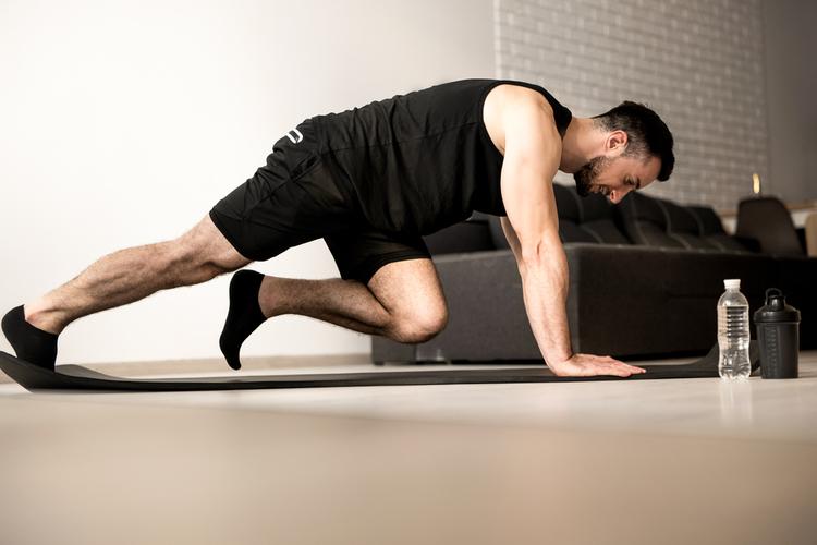 Man doing mountain climber exercises on black yoga mat.