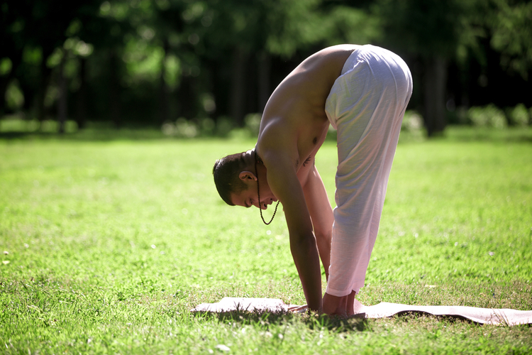 Profile of sporty young man exercising in park doing yoga.