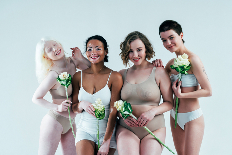Group of multiethnic women with different kind of skin posing together in studio getting body compliments.