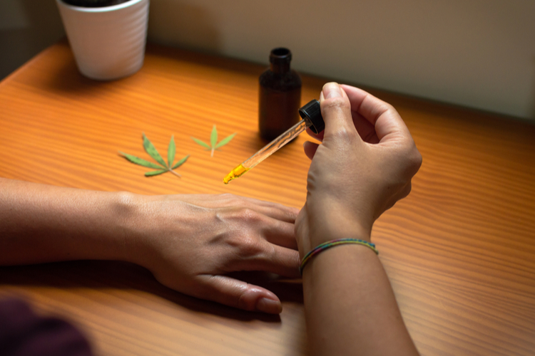 Woman pouring CBD oil on her hand to test the product.