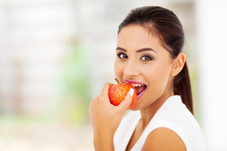 Woman eating an apple.