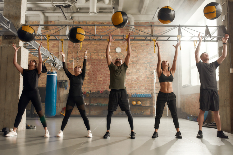 Group of fit individuals using exercise ball while having workout at industrial gym.