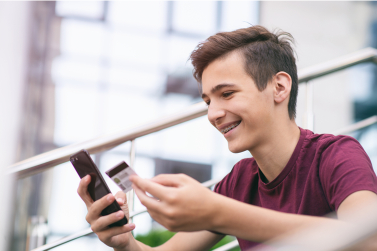 Teenage boy with greenlight debit card and mobile phone makes purchasing outdoors.