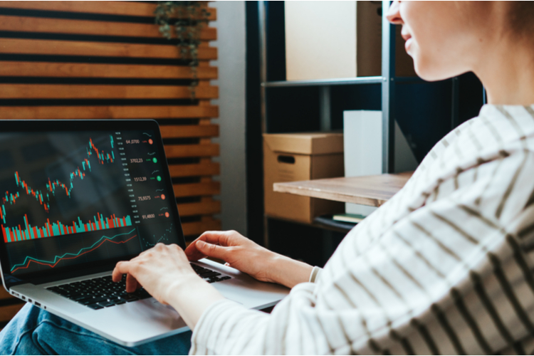 Woman investing in world stock market, using her laptop and m1 finance at home.