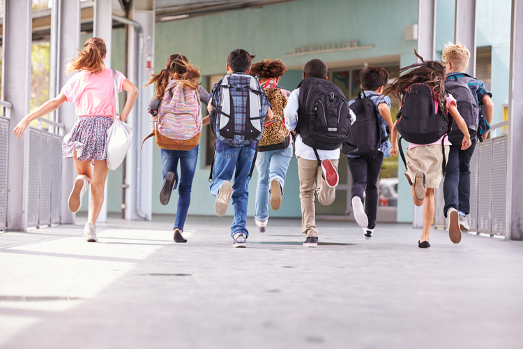 Group of elementary school kids running at school on national school backpack awareness day.