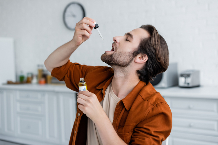 Side view of man taking cbd oil at home.