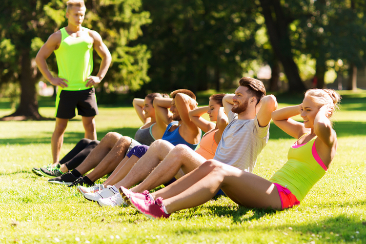 Group of people doing group exercise outdoors.