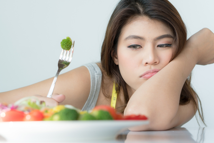 Woman looking at her food getting tired of different diet trends.