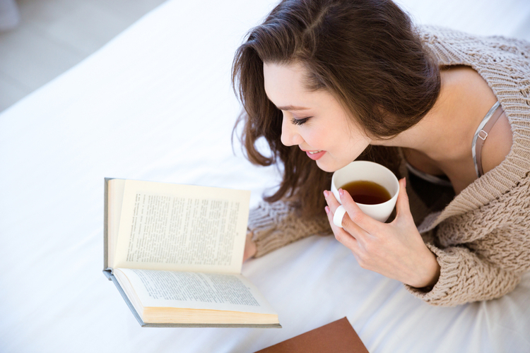 Woman reading book and drinking coffee on bed.
