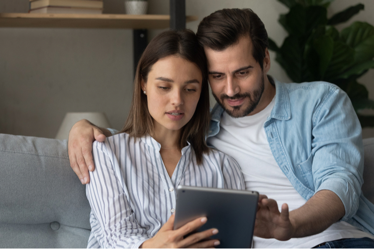 Focused married couple read insurance policy loan contract text from bank website on tablet.