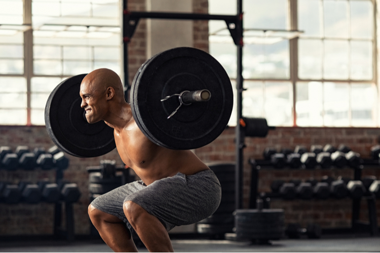 Muscular African-American man taking efforts to lift weight barbell in fitness center, boosting his testosterone levels.