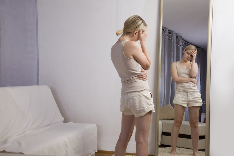 Woman looking at her reflection in the mirror, having problems with body shaming.