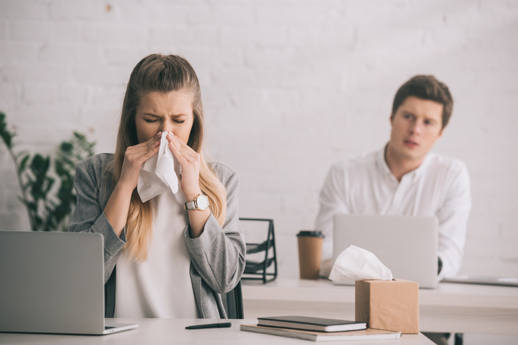 Businesswoman sneezing in tissue near coworker in office reacting to workplace stress.