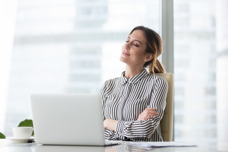 Smiling businesswoman sitting in office chair relaxing with eyes closed.