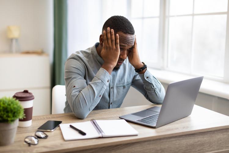 Stressed man businessman at laptop touching head.