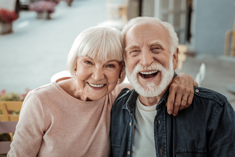 Joyful nice elderly couple smiling while being in a great mood after world smile day activities.