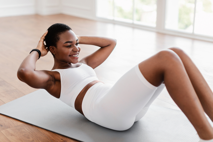 Woman smiling while doing yoga for bodybuilders.