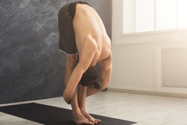 Sporty man doing Standing Forward Bend posture.
